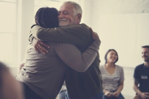 two people hugging in a Caregivers Support Group