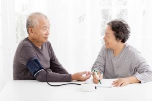 Health Advocate Checking Blood Pressure of Senior Man