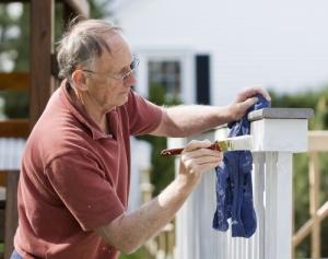 Senior Man Painting Deck doing minor home repairs