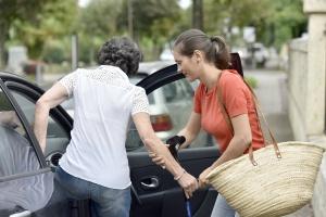 women helping elder take a senior transportation