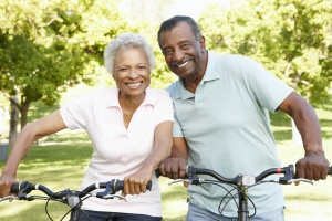 happy couple who is Aging In Place together on a bike ride