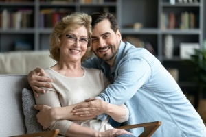 mother and son sitting on couch while he is Caring For Aging Parents