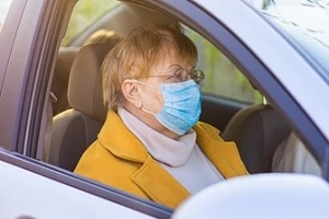 old lady in car wearing mask during Senior Transportation Service